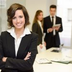 Businesswoman leader looking at camera in working environment. Young woman wearing black blazer jacket