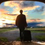 Foto de un chico que camina con una maleta hacia el sol